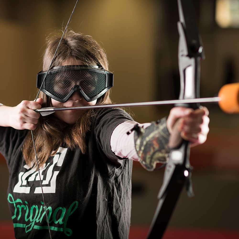 Jente som spiller archery tag
