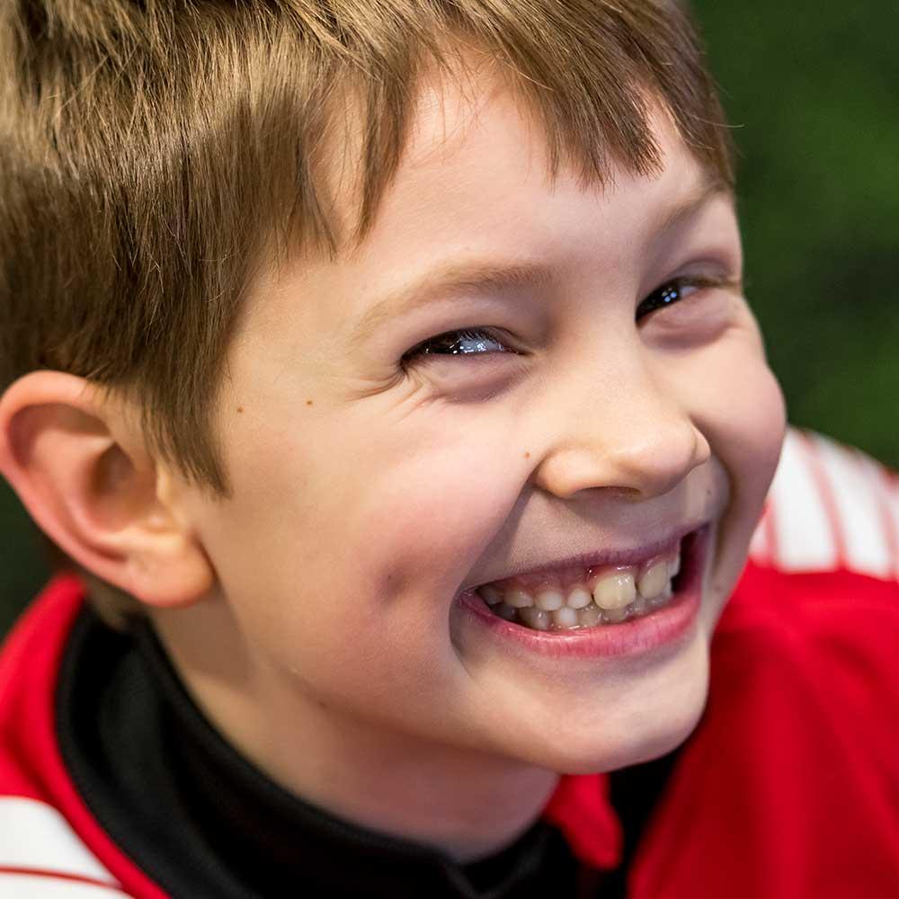 gutt som smiler. foto.