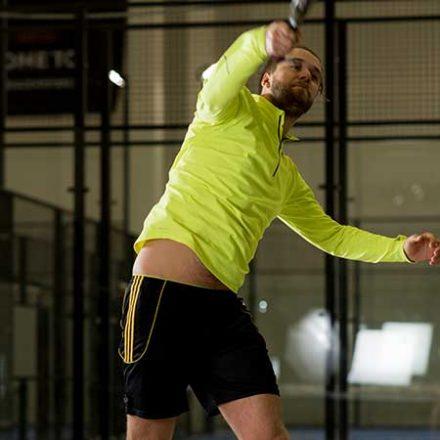 Person som hopper for å nå ballen med rakketen. Bilde.